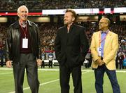 R.C. Slocum, former Aggies coach, from left; rock star John Mellencamp; and Percy Vaughn with KIA bring out the teams' ceremonial game ball.