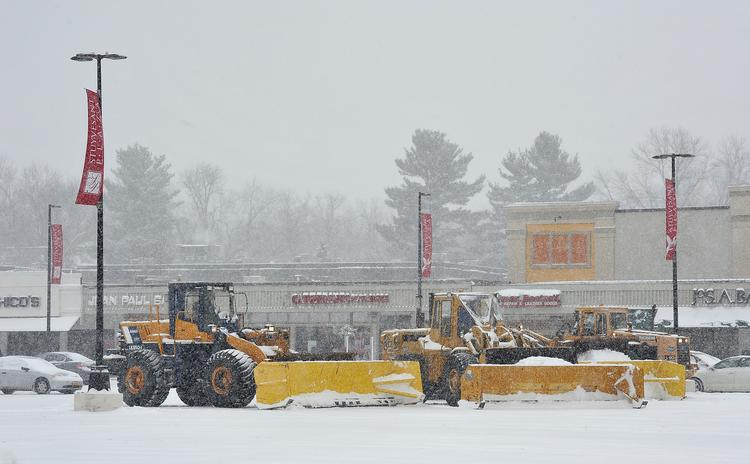 A crew clears snow at Stuyvesant Plaza, just outside Albany, NY, on Thursday. A winter storm warning remains in effect until 10 a.m. Friday.