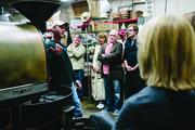 Stauf's Head Roaster Tommy Goetz, left, talks about the coffee bean roasting process used by the company, which sells coffee wholesale as well as in its retail stores.