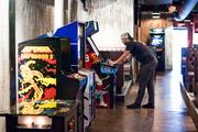 Bar Manager Michael Casper warms up the video games a few weeks before the grand opening.