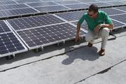 Supergreen Solutions founder Sean Cochrane checks solar panels on a roof.