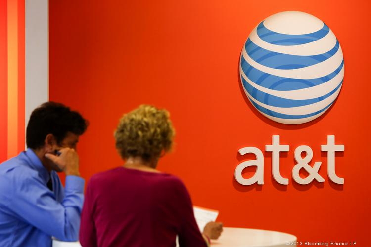 An employee helps a customer at an AT&T store in Manhattan Beach, California, on Monday, July 22, 2013. AT&T is trying to lure customers away from T-Mobile.