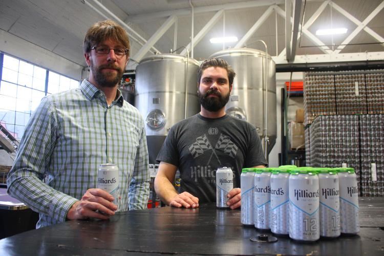 Hilliards Beer co-founders Ryan Hilliard (left) and Adam Merkl in their Ballard microbrewery with the brewery's best-selling '12th Can' pale ale, brewed for Seattle Seahawks football fans.