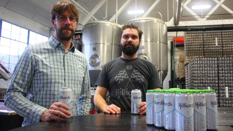 "Hilliard's Beer co-founders Ryan Hilliard (left) and Adam Merkl in their Ballard microbrewery with the brewery's best-selling ""12th Can"" pale ale, brewed for Seattle Seahawks fans. Hilliard's is one of dozens of local breweries participating in Seattle Beer Week."