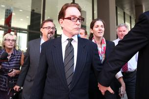 Beanie Babies founder Ty Warner is escorted from the Dirksen U.S. Courthouse in Chicago on October 2, 2013. Warner entered a guilty plea for tax evasion, apologizing in a choked-up voice and telling a federal judge he had known his tax forms weren't accurate.