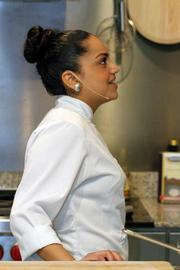 "Lexington College student chef Hillary Marquez prepares a faro stuffed peppers dish as winner of the ""pursuit of palate"" competition created by Vigo-Alessi. She is working in the company's newly renovated kitchen in Tampa. Here she is looking up at a camera."