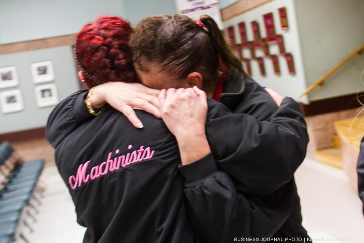 """With tears rolling down her cheeks, a disappointed Hazel Powers (right) hugs Gabrielle Rogano after union officials announced that the Boeing contract proposal passed by a 51 percent yes vote Friday night. Both union members had voted against the deal. """"All the benefits that come along with being in solidarity have been taken away by 51 percent,"""" Powers said."""