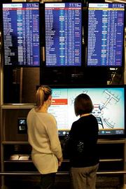 Many passengers learned of their flight cancellations after arriving at Logan Monday. Two passengers survey the damage.