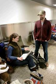 Emily White and Noel Stout of Seattle just learned they are unlikely to get a return flight home until Friday.