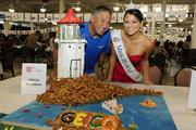 Ron Addington, marketing director for GEICO Insurance for Hawaii and Alaska, and Miss Hawaii Crystal Lee pose with a lighthouse made of gingerbread at the Easter Seals Hawaii Gingerbread Family Festival 2013 at the Neal S. Blaisdell Center.
