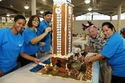 Central Pacific Bank executives, from left, Sonya Gomes, manager of deposit servicing; Carol Kamai, collection manager; Mike Liftee, collection supervisor; Bill Wilson, executive vice president; and Adrien Chee, head of information technology operations, work on decorating a gingerbread model of Aloha Tower at the Easter Seals Hawaii Gingerbread Family Festival 2013.