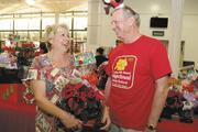 Val O'Brien, left, a member of the Easter Seals Hawaii board of directors and development committee, and Dick Sears, chairman of the board, look over various plants and baskets at the  organization's Gingerbread Family Festival 2013 at the Neal S. Blaisdell last month.