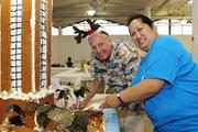 Central Pacific Bank's Bill Wilson, executive vice president, left, and Adrien Chee, head of information technology operations, work on a gingerbread model of Aloha Tower at Easter Seals Hawaii's Gingerbread Family Festival 2013 at the Neal S. Blaisdell Center last month.