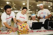 Longs Drugs/CVS CareMark executives, from left, Jon Higa, senior operations manager and Darcey Moniz, category manager put on the candies for a gingerbread house while CVS CareMark executive Wendalyn Russ-Cook, supervisor for commercial prior authorization and Robert Cook, volunteer for event, check in on registration for Easter Seals Hawaii Gingerbread Family Festival 2013 at the Neal Blaisdell.