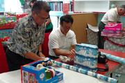 The Graham Builders team wrapped more than 100 holiday gifts for the children and families of the Hawaii Children's Cancer Foundation before the annual holiday party at Kapiolani Medical Center for Women and Children. From left, Randy Aina, Hawaii Children's Cancer Foundation Board president, and Evan Fujimoto, president of Graham Builders.