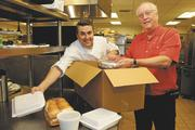 Eric Leterc, left, executive chef at the Pacific Club, and Richard Emery, president of Hawaii First, prepare a gourmet turkey dinner to-go for the 5th Annual Christmas Giving Program for Hawaii First. Emery said Hawaii First raised $30,000 from vendors, employees and friends to support its mission of providing meals to support eight nonprofits.