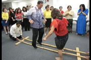 Island Insurance executives Wayne Hikida and Sharon Lee entertain employees, clients and friends with the traditional Filipino tinikling bamboo dance during the company's employee lunch hour fundraiser, which raised nearly $5,500 for the Aloha for Philippines relief effort.