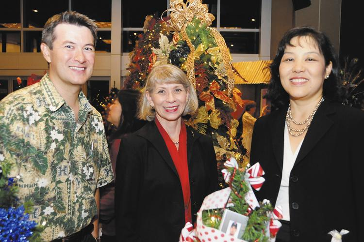 """From left, Dave Mori, director of development for the University of Hawaii Cancer Center; Donna Vuchinichi, president and CEO of the UH Foundation and Stacy Wong, director of communications and external affairs for the UH Cancer Center, attend the inaugural """"Trees by the Sea"""" a benefit  for the center. Decorated trees, wreaths and poinsettia by local designers were available for sale and auction."""