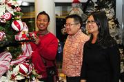 """From left, Christmas tree designer Cliff Duldulao shows Jason Nagai and Lynn Takahashi, board members of the Friends of the University of Hawaii Cancer Center, his """"Candy Train Tree,"""" which had a train that operated and traveld around the tree at the inaugural """"Trees by the Sea""""  benefit for the center."""