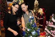 """Lynn Takahashi, left, and Mona Wood of Ikaika Communications, admire the """"Hawaii Five-0"""" tabletop tree on display at the inaugural """"Trees by the Sea""""  benefit for the University of Hawaii Cancer Center."""
