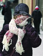 A pedestrian stays bundled up while talking on a cell phone and walking along Liberty Avenue in downtown Pittsburgh.