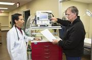 Dr. Nguyen Luu, left, and emergency room director Richard Burton make final preparation for the opening of the Apollo Hospital emergency room. The facility's cancer treatment center opens Jan. 13.