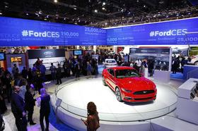 A Ford Mustang vehicle is displayed at the Ford Motor Co. booth as attendees view information about Ford Sync AppLink at the 2014 Consumer Electronics Show (CES) in Las Vegas, Nevada, U.S., on Tuesday, Jan. 7, 2014.