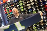 Rick Blohm, owner of the Sports Den, folds a 12th Man Seahawks flag. Sales have been brisk, and it's hard to keep up the inventory of some items.