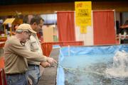 Vendors Gary Westergren (left) and Ian Tolmay tried their luck at the trout pond in St. Paul's Roy Wilkins Auditorium.