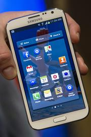 A Facebook Inc. employee holds a phone that is running the new Home program.