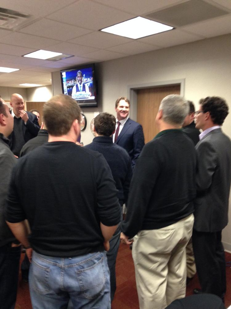 Jay Gruden, far center, talks with Redskins beat reporters Thursday night, after delivering pizzas for a tired and starved press corps.