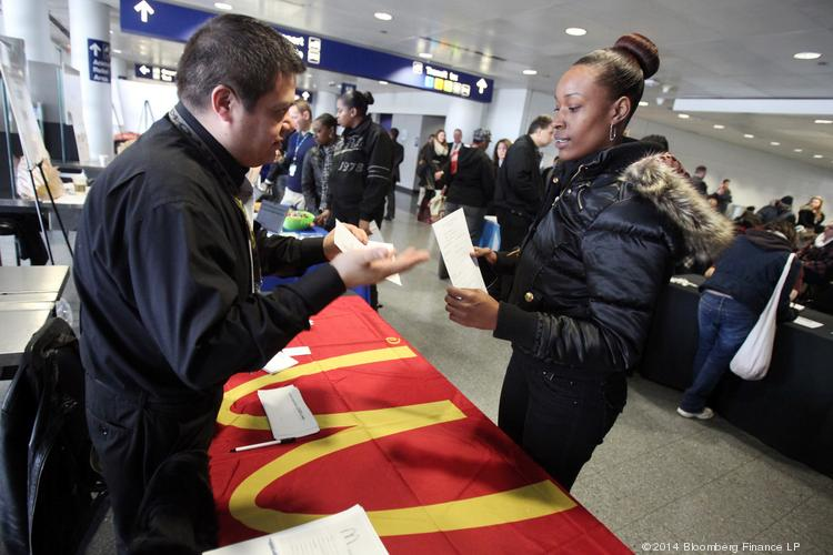 A job seeker, right, talks with a McDonald's Corp. representative at a job fair in Chicago on Jan. 13, 2014.