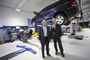 Owner Chuck Theisen, left, and General Manager Al Lemoine show the climate-controlled service area of the new dealership.