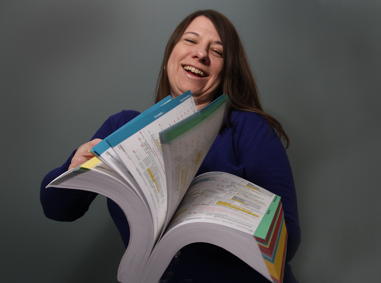 Jennifer Ellis of The Portland Clinic holds the new medical code book, ICD-10, which has more than 1,000 pages.