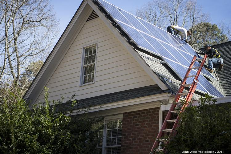 Sun Dollar Energy of Raleigh, seen here installing solar panels on a home, is a small business concerned about being pushed out of the market by Solarize programs.