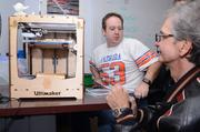 Pat Starace (far right) watches as FamiLab board member Matt Armstrong makes adjustments to a 3-D printer he built at the lab about 18 months ago.