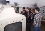 FamiLab-ers gather at a CNC machine that is being refurbished in the machine shop.
