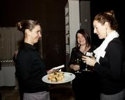 A server at Ella offers food at the Book of Lists party.