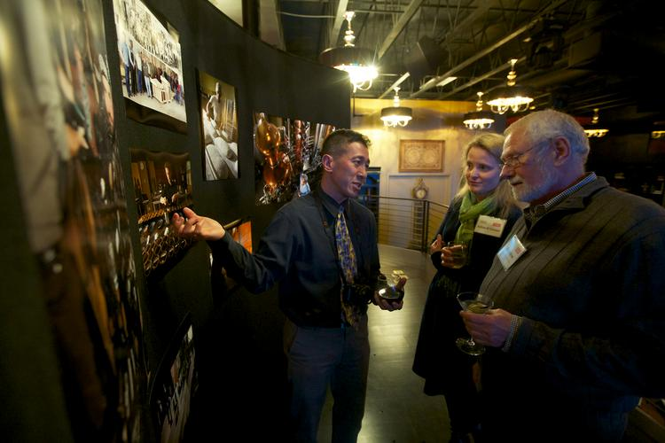 From left, Anthony Bolante of the Puget Sound Business Journal and Esther O'Connor and Roy DuBrow of the British Motor Coach Co., talk about the changing Sodo neighborhood at the Faces of Sodo reception at Aston Manor in Seattle on Thursday.