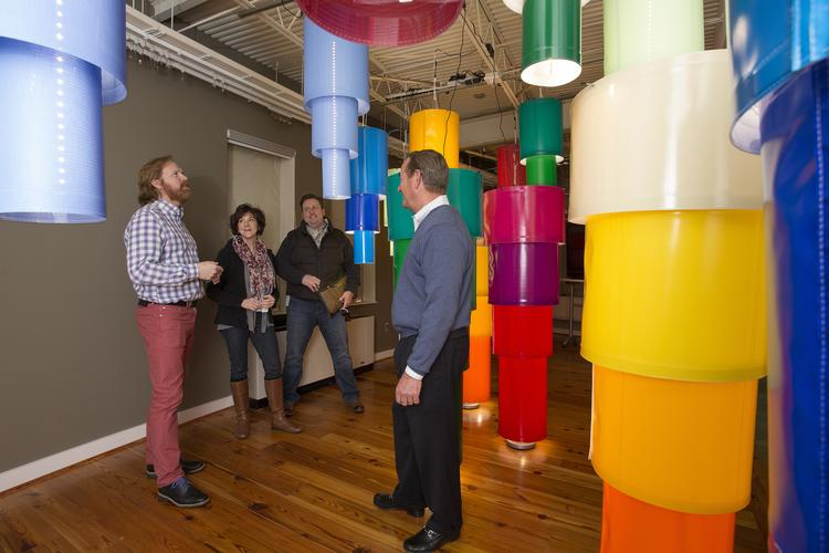 In the Concept Gallery at Glen Raven, Greg Voorhis, left, design  manager with Glen Raven, and Ralph Allen, right, with Glen Raven Homecraft Sales, show clients Patti Frye and Zachary Bryan of Lane Venture a display of fabrics used to make lamp shades.