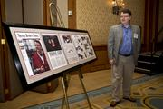 Wingo stands next to a display featuring TBJ's Businessperson of the Year coverage.