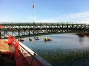 Kayaks and other boats assemble near the not-yet-open pedestrian bridge across the channel.