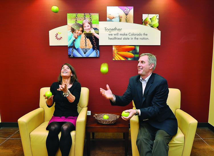 Kelly Dunkin, vice president, philanthropy, and Jesse Wolff, director, private sector initiatives, juggle apples at the Colorado Health Foundation.