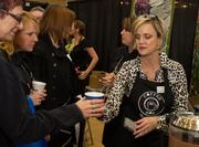 Dee Anna Arbuckle, director of sales for the Hotel at Waterwalk, hands out coffee and speaks with guests at the Meet Wichita Expo Thursday at the Mid-America All Indian Center, 650 N. Seneca St.