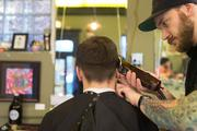 "Justin ""Jut"" Francis, who has worked at Old Bank Barbers for six months, gives a client a trim Tuesday afternoon."