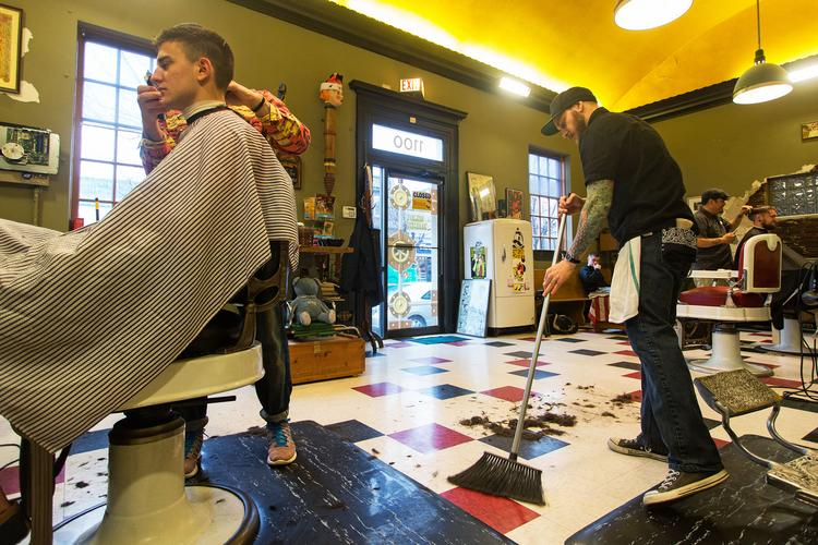 "Justin ""Jut"" Francis, who has worked at Old Bank Barbers for six months, sweeps the floor as owner Daniel Wells works with a client."