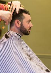 Old Bank Barbers owner Daniel Wells works on a client Tuesday afternoon at the Hampden shop.