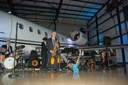 A large executive jet looms behind the Mark McKenzie Quartet playing at the DBJ Book of List party at the Starbase hangar in Addison.