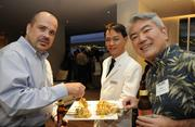 Attorneys David Squeri, left, and Rex Fujichaku try a chicken skewer with yellow curry offered by Tom Tang, banquet server at The Modern Honolulu.