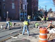 MPD workers pour concrete on Elm Street, near Tiffin Alley.